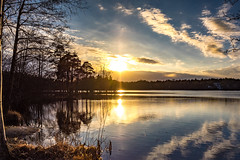Spring sunset (Jens Haggren (off for a while)) Tags: sun sunset sky clouds water reflections trees silhouettes landscape view myrsjön nacka sweden jenshaggren