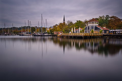 Fall at the Fjord // Flensburg (//Sebastian) Tags: wood longexposure blue autumn red lake reflection fall church colors yellow skyline germany denmark restaurant mirror harbor boat town cafe october ship quiet cloudy harbour terrace calm fjord reflexion bellevue firth stadthafen flensburg langzeit cittipark hafenspitze hafendamm imjaich ostufer flensburgfjord flensburgfirth amkanalhafen forgotthedustspotsagain