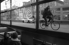 Multitasking (Ivan Rigamonti) Tags: blackandwhite zurich streetphotography zurichmainstation biking street switzerland bike traffic smartphone multitasking woman shopping bw man outdoors europe urban urbanexploration ivanrigamonti