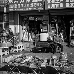 Bang Bang (Go-tea 郭天) Tags: qingdao huangdao old man saler seller shop table small sun sunny winter cold shadow fireworks fire craks tradition traditional cny new year business work worker duty alone lonely waiting wait customer money boxes packs hat coat seat seated motorbike motobike mess messy street urban city outside outdoor people bw bnw black white blackwhite blackandwhite monochrome asia asian china chinese shandong canon eos 100d 24mm prime