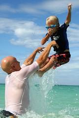 riding the air (lucy96734) Tags: family b water fun hawaii drops interestingness dad child splash noseplug lanikaibeach goofykid throwyourkidsintheair kidintheair hecangounderwaterwithoutplugginhisnose hechoosesnottowhenthrown