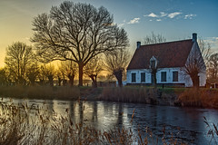 The sun is setting over the frozen Damme Canal (Roland B43) Tags: damme damsevaart canal frozen winter minolta35105mm