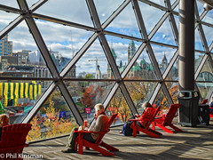 Lunch break at the conference centre-.jpg (Phil Kinsman (Olwebhound)) Tags: ottawa ontario canada shawcentre ottawacongresscentre streetphotography parliamentbuildings rideaucanal conferencecentre redchair adirondackchair panasoniclumixgm5 bluesky sunnyday clouds architecture