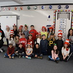 Student poses with elementary students on Dr. Seuss day