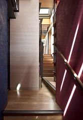 shafts of light play on the polished plaster of the stairwell including mirrored view into living area