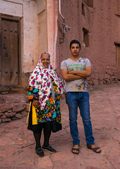portrait of an iranian woman wearing traditional floreal chador with her son in zoroastrian village, Isfahan Province, Abyaneh, Iran (Eric Lafforgue) Tags: flowers portrait people woman man tourism wearing vertical clothing village veil dress iran muslim islam traditional headscarf mother middleeast son clothes elderly covered shia iranian tradition cloth aging abyaneh 2people twopeople chador traditionalclothing 30sadult persiangulfstates abiyaneh floreal 60sadult lookingatcamera  fulllenght  16547 colourimage  iro isfahanprovince redvillage  westernasia  natanzcounty