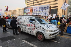 """Seoul Korea Kwanghwamun candle rally January 7 2017 rally with posters and painted vehicles - """"Van With A Plan"""" (moreska) Tags: seoul korea kwanghwamun candlelight rally democracy protest freespeech march socialchange slogans vehicle van graffiti spraypaint hangul graphics flags unstaged candid publicsquares afternoon winter 광화문 capital 대한민국 rok asia"""