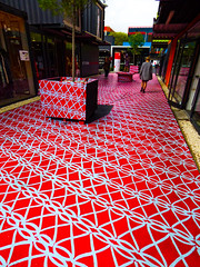 No Longer in a Holding Pattern (Steve Taylor (Photography)) Tags: walking away art design mural streetart path red white sad paint lady woman newzealand nz southisland canterbury christchurch city cbd tree perspective pattern artwork buzzcarpet jannavanhasselt reactivate stiches crochet