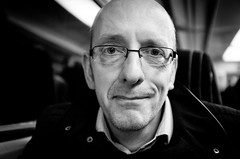 2015_328 (explored) (Chilanga Cement) Tags: portrait blackandwhite bw man train glasses friend fuji trains commuter spectacles enigmatic uclan xseries x100t fujix100t forensicgeneticist