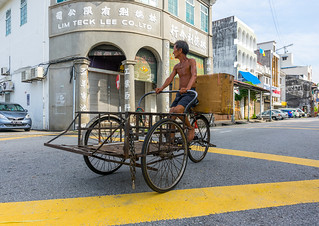 Skinny man rickshaw pedalling through chinatown, Penang island, George town, Malaysia