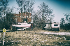 Parked Traveler (CJ Schmit) Tags: wwwcjschmitcom eosm3 canon canoneosm3 mirrorless cjschmit cjschmitphotography canonefm1855f3556isstm photographermilwaukee milwaukeephotographer photographerwisconsin racine racinephotographer kneeland wisconsin winter abandoned forgotten boat rv grass urbandecay 7mileroad landscape urbanexploration urbex country outdoors outside sunny nikanalogefex2 cold trees