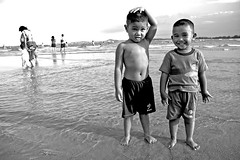 Simply smile, bro' (Wen Nag (aliasgrace)) Tags: sea summer portrait bw beach boys water smile comfortable kids 1025fav 510fav pose blackwhite asia southeastasia asians brothers head topv1111 strangers posed siblings malaysia males bathing uncomfortable uneasy southchinasea cherating cjildren topvaa top20flickrkidshof top20kidsphoto youvsthebest thepinnaclehof