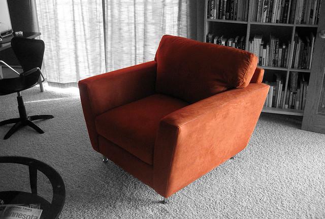 orange carpet chair furniture books livingroom drapes