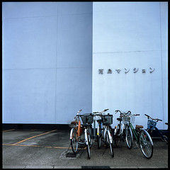 gossip in the parking lot ((mjh)) Tags: 120 6x6 tlr film japan mediumformat square concrete parkinglot fuji minolta bikes bicycles nagoya mansion aichi provia100f twinlensreflex autocord rokkor mamachari 75mmf35 utataliveshere