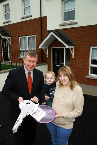 DSD Minister Mervyn Storey MLA hands the keys of her new home at Church View Charlemont to Nicole Campbell & son Oliver