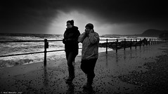 Hang on to your hats girls. (Neil. Moralee) Tags: sidmouthdevonneilmoralee storm woman women walk hat wind sea waves gale cold cloudy dark winter sidmouth esplanade devon two twin duo nikon d7100 neil moralee rain weather rough force 18300mm black white blackandwhite bw mono monochrome lashed