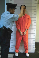 Instructing prisoner to take mug shot (asiancuffs) Tags: handcuffs handcuffed arrest arrested inmate prisoner shackles shackled