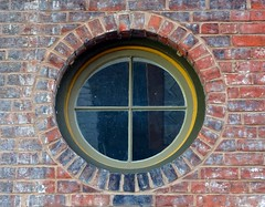 Round Window (Jae at Wits End) Tags: old red reflection building brick window glass architecture america circle outside mirror exterior outdoor decay kentucky arc structure pale southern faded american round worn weathered opening portal curve paducah bleached circular brickwork faint washedout discolored
