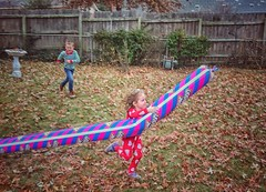 The girl can run! (Pejasar) Tags: kids fun children birdbath boy girl chase fence balloon leaves granddaughter run