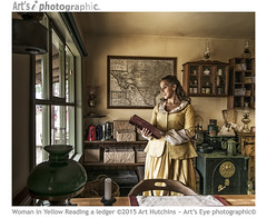 Woman in Yellow Reading a ledger (Art's Eye photographic) Tags: window lamp shop book chair candle basket post mail cabinet desk furniture map naturallight parcels western safe wellsfargo trunks brunette shelves tins broom correspondence cases ledger oillamps strongbox frontiertown westerntheme interiorshoot