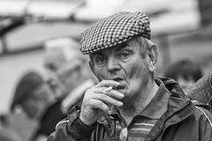 Whaaas up ? (Frank Fullard) Tags: frankfullard fullard portrait candid street cap cigarette smoker caught inhale look mono blackandwhite ballinasloe fair horsefair irish ireland galway startled