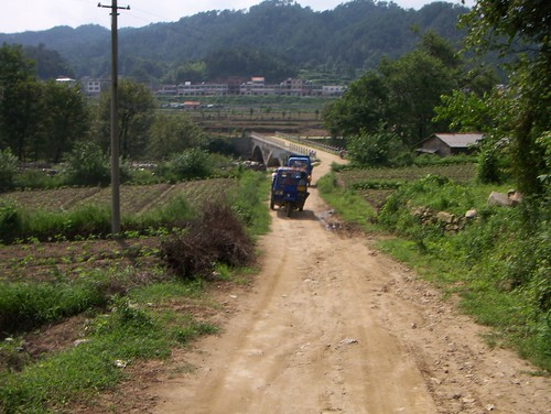 3-wheeled chinese tractor/trucks traveling up country dirt road