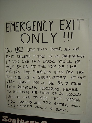 EMERGENCY EXIT ONLY!!! Do NOT use this door as an exit unless there is an emergency. If you use this door, you'll be met by us at the top of the stars and possibly held for the police as a shoplifter. At the very least, you'll be 86'd from both Recycled Records, never to return. Neither of us would like to see that happen, now would we? After all, the stuff's only a buck...