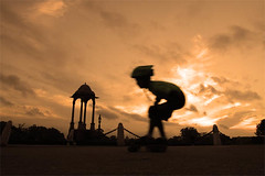A Boy Skating at India Gate (Captain Suresh Sharma) Tags: road morning travel red sky orange india holiday game monument silhouette sport sunrise dawn kid child play bend spirit delhi wheels helmet competition practice canopy perfection kneepads bending indiagate physicalexercise