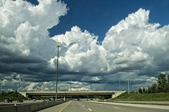 Massive clouds over the highway (fool's itch) Tags: highway traffic bluesky skyandclouds lampposts htt dramaticclouds electricpoles highway407 outdoorshot