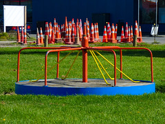 Waiting For Playtime (Steve Taylor (Photography)) Tags: roundabout cone road traffic street park orange yellow white blue green fun metal plastic newzealand nz southisland canterbury christchurch city grass playground crowd group
