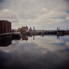 Canning Dock (sonofwalrus) Tags: ocean uk sea england film water architecture clouds liverpool buildings holga lomo lomography dock overcast scan reflextion canningdock