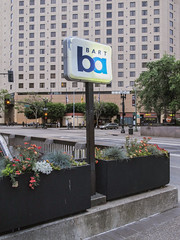 """Aged half-backlit """"Small BART, large ba"""" plastic. (Tim Kiser) Tags: 11thstreet 11thandbroadway 12thstreetoaklandcitycenterstation 12thstreetoaklandstation 12thstreetstation 1983 1983architecture 1983building 1983hotel 2015 20150702 alamedacounty alamedacountycalifornia bart bartstation bayarea bayarearapidtransit bayarearapidtransitstation broadway california eastbay img6043 july july2015 oakland oaklandcalifornia oaklandmarriottcitycenter oaklandmarriottconventioncenter sanfranciscobayarea ba backlitplastic backlitplasticsign downtown downtownoakland flowers hotel hotelwindows intersection northerncalifornia paved pavement planters stoplights street subwaysign subwaystation subwaystationentrance subwaystationsign trafficlights trafficsignals"""