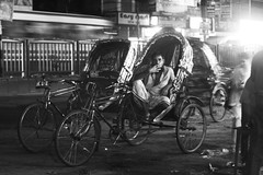 a late night rikshawa puller sitting on his rikshawa after day long work. I saw him smoking cigarette to thinking like what the f__k is life (দূর্লভ) Tags: