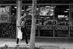 Tempting (burnt dirt) Tags: houston texas downtown mainstreet city town street streetphotography girl woman people person bw building office restaurant walking purse food bag tree sidewalk fujifilm xt1