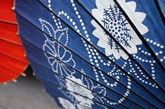Pontocho parasols (Eric Flexyourhead) Tags: pontocho 先斗町 nakagyoku 中京区 kyoto 京都市 kansai 関西地方 japan 日本 city urban backstreet detail fragment parasol umbrella japanese blue indigo red vibrant vivid shallowdepthoffield ricohgr