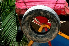 peeking (Farl) Tags: travel heritage colors river boat chains eyes paint delta tire palm vietnam peek tradition mekong portals