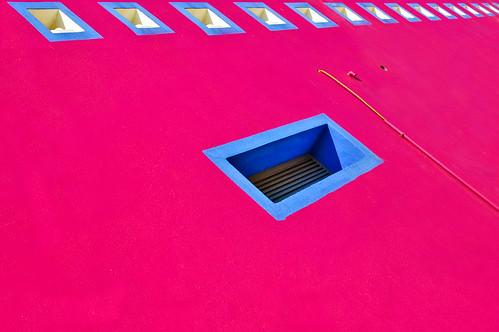 Fotografía de una pared rosa con ventanucos pintados en azul y un cable amarillo