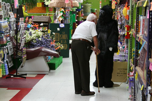 Older Gentleman Smelling Gorilla Suit