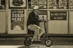 Understanding the Basics (Jon Scherff) Tags: street people sepia candid streetphotography scooter transportation storefront schwinn electricscooter nikond810 schwinnscooter schwinns500