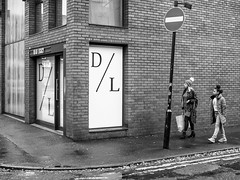 Northern Quarter #147 (Peter.Bartlett) Tags: manchester niksilverefex woman unitedkingdom wall people walking corner doorway urbanarte urban monochrome door text lunaphoto doubleyellowlines girl streetphotography candid uk m43 microfourthirds peterbartlett bw olympuspenf sign blackandwhite noiretblanc city