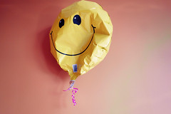 a little deflated, but still smiling (KevinIrvineChi) Tags: art popart pop resist trump smiley face balloon deflated yellow orange wall indoors indoor pink ribbon still life inside sony dscrx100 2017 next four years shadow eyes smile round mylar curled curly flickrsocial flickrheroes