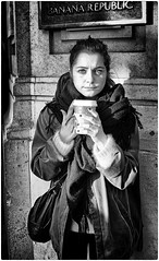 Nice and Warm (Steve Lundqvist) Tags: street woman donna england inghilterra uk english bw blackandwhite black white shadow light lighting london londra monochrome glass hand beverage drink drinking coffee cafe caffe cappuccino streetphotography portrait shot snap ritratto girl beauty sciarpa scarf winter cold warm nice eyes beautiful united kingdom banana republic people eyecontact