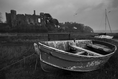 Laugharne Castle and Boat (Jon and Sian Bishop) Tags: trees sky blackandwhite cloud black blur building castle monochrome grass stone southwales wales clouds canon buildings bench landscape eos grey boat focus paint flat seagull south bricks salt rope row sail whit marsh derelict saltflats laugharne wodden 2015 eos550d