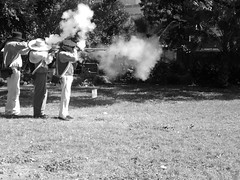 the cloudmakers (vfrgk) Tags: men firing shooting rifles smoking powder firearms representation americanhistory frontiersman monochrome bw blackandwhite thealamo sanantonio tx santaanna davycrockett muskets fire musketeers people military reenactment heritage smoke sunny lightandshadows urbannature performing streetperformer performers