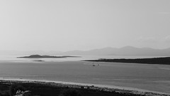 Dreamily in the sunshine (RIch-ART In PIXELS) Tags: scotland peninsula newulva leicadlux6 dlux6 leica blackandwhite monochrome sea isle shore coastline light sunlight hazy landscape seascape atlantic ocean sailboat unitedkingdom schotland kilmory coast water