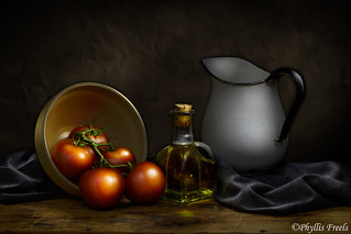 Still life with tomatoes, oil cruet, and white pitcher.