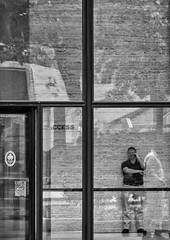 'Ubiquitous' (Canadapt) Tags: man mobile phone window door reflection city street building bw toronto canadapt