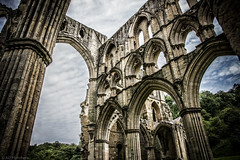 Where saintly songs soar (Anthony P26) Tags: architecture category decay england internal northyorkshire places rievaulxabbey travel yorkshire travelphotography architecturephotography ruin derelict dissolution abbey monastery placeofworship english british britain greatbritain uk unitedkingdom sky cloudysky whiteclouds trees valley countryside rural canon canon1585mm canon550d outdoor arches arch gothicarchitecture column building wow