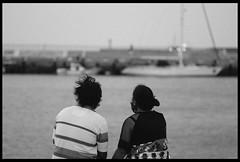 Couple watching the sea. (ykpopy2011) Tags: people blackandwhite bw woman white man black film monochrome pentax bokeh snapshot taiwan f18 77 taoyuan 黑白 fa 永安漁港 街拍 yonganfishingport 單色 pentaxfa77f18limited