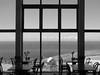 (Kelvin P. Coleman) Tags: canon powershot cornwall coast shore sea water café restaurant tables chairs window frame grid lines summer afternoon sky horizon blackandwhite monochrome bw noiretblanc schwarzweiss blancoynegro indoor
